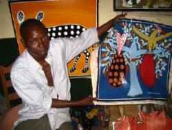 Daudi TingaTinga holding one of his paintings